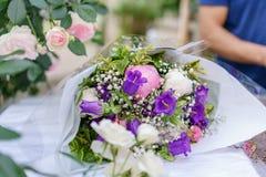 Härlig bukett i blomsterhandel utomhus- arbete i blomsterhandel assistent i studion för blom- design som gör garneringar Royaltyfria Bilder