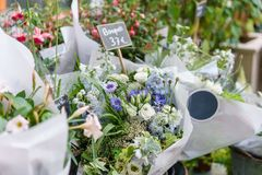 Härlig bukett i blomsterhandel utomhus- arbete i blomsterhandel assistent i studion för blom- design som gör garneringar Arkivbild