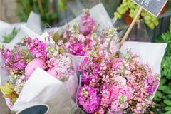 Härlig bukett i blomsterhandel utomhus- arbete i blomsterhandel assistent i studion för blom- design som gör garneringar Arkivbilder