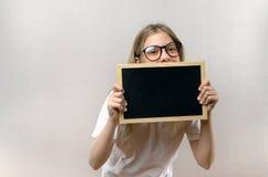 H?rlig busig flicka med exponeringsglas som in rymmer ett tecken hennes h?nder Kopia-utrymme royaltyfri bild