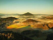 Härlig bygd av Tjeck-Sachsen Schweiz parkerar Försiktig dimma ovanför bykyrka Varma solstrålar slåss med förkylning jordmis Royaltyfri Fotografi