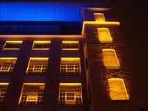 Härlig byggnad som är upplyst i guling som är röd och blått Royaltyfri Foto