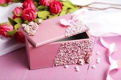 Härlig casket med blommor på purpurfärgad träbakgrund Fotografering för Bildbyråer