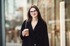 Härlig caucasian affärskvinna som går till kontoret på stadsgatan med bärande exponeringsglas för kaffekopp arkivbild