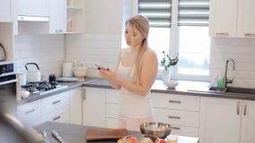 Härlig caucasian flicka i den vita skjortan och rosa matlagning i det ljusa köket som talar på mobiltelefonen och le stock video
