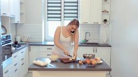 Härlig caucasian flicka i den vita skjortan och rosa matlagning i det ljusa köket som talar på mobiltelefonen och le lager videofilmer