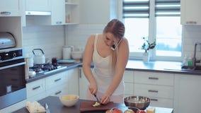 Härlig caucasian flicka i den vita skjortan och rosa matlagning i det ljusa köket som talar på mobiltelefonen och le arkivfilmer