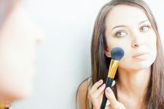 Härlig caucasian kvinna eller makeupkonstnär som gör sminket själv arkivbild