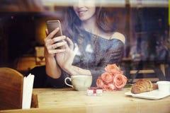 Härlig caucasian kvinna med långt hår genom att använda mobiltelefonen som sitter i kafé St Dag för valentin` s royaltyfria foton