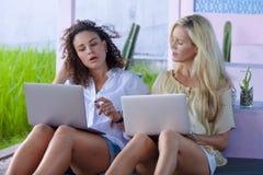 Härlig caucasian kvinna och attraktiv afro latinsk blandad flicka som direktanslutet utomhus arbetar samman med bärbar datordator fotografering för bildbyråer