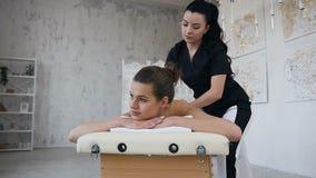 H?rlig caucasian kvinna som kopplar av under massage p? baksidan i brunnsortsalong lager videofilmer