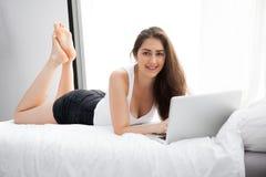 Härlig Caucasian kvinna som lägger ner på vit säng genom att använda bärbara datorn och leende royaltyfria bilder