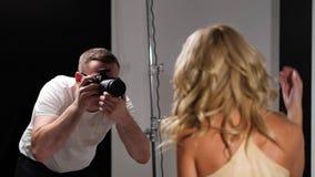 Härlig caucasian kvinna som poserar för fotograf i studio arkivfilmer