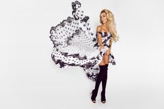 Härlig caucasian modemodell som bär en vit klänning med svarta prickar på en vit bakgrund i studion arkivbilder