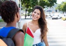 Härlig caucasian student som talar med afrikansk amerikangirlf fotografering för bildbyråer