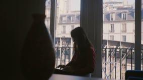 Härlig Caucasian vdaffärskvinna som använder bärbara datorn som sitter på lägenhetfönstret i Paris med fantastisk gammal hussikt stock video