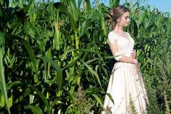 Härlig charmig flicka i beige klänning i havre på fält Royaltyfri Fotografi