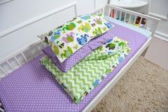 Härlig children& x27; s-säng i olika färger Arkivfoton