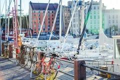Härlig cityscape, cyklar på stranden, en port med boaen royaltyfria foton