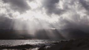 Härlig cloudscape med stor byggande moln och solnedgång bak glänsande solstrålar och sjön vinkar stock video