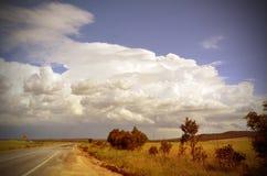 Härlig cloudscape och storm över vägen till och med bygd arkivfoto