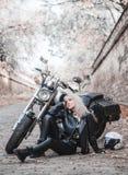 Härlig cyklistkvinna som är utomhus- med motorcykeln arkivbilder
