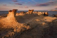 Härlig Cypern solnedgång på den tomma steniga kusten för öken med konstiga fiqures på den Halk stranden Arkivbild