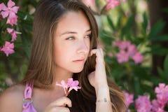 Härlig dam i en headshot, innehav och spela med en blomma Arkivfoton