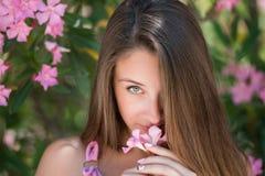 Härlig dam i en headshot, innehav och spela med en blomma Arkivbilder