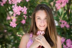 Härlig dam i en headshot, innehav och spela med en blomma Royaltyfria Bilder