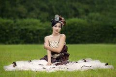 Härlig dam i kappa på grönt fält Royaltyfria Foton