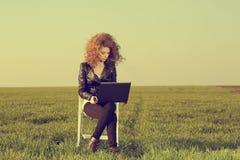 Härlig dam med hennes bärbar dator på gräs Arkivbild