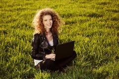 Härlig dam med hennes bärbar dator på gräs Arkivbilder