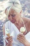 Härlig dam som äter glasssammanträde på en deckchair Arkivbilder
