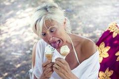Härlig dam som äter glasssammanträde på en deckchair Fotografering för Bildbyråer