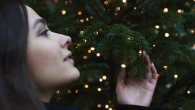 Härlig dam som drömmer nära julgranen som gör önska i vinterferier arkivfilmer