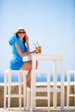 Härlig dam som dricker kallt kaffe som tycker om havssikt Den härliga kvinnan kopplar av under europeisk havssemester på stranden Royaltyfria Bilder