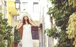 Härlig dam som går ner gatan i en vit klänning Fotografering för Bildbyråer