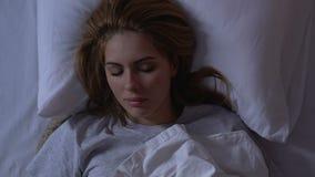 Härlig dam som ligger i säng på natten, hemtrevlig sund sömn på den bekväma madrassen stock video