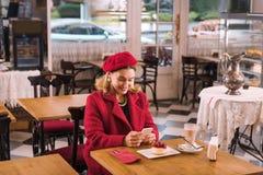 Härlig dam som smsar hennes make som väntar på honom i kafé arkivfoto