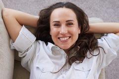 Härlig dam som tycker om fri tid som ligger på soffan Royaltyfria Bilder