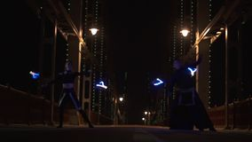 Härlig dans med ledd poi av cirkuskonstnärer man och kvinna på den tomma bron lager videofilmer
