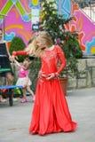 Härlig dansare i en röd klänning Härlig ung flickadans i en röd klänning Dans offentligt Den begåvade ungen gör dansen arkivbild