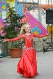 Härlig dansare i en röd klänning Härlig ung flickadans i en röd klänning Dans offentligt Den begåvade ungen gör dansen royaltyfri fotografi