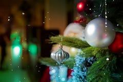 Härlig dekorerad julgran framme av den brinnande spisen på huset Fokus på spisen Metalliska struntsaker Arkivfoton