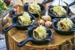 Härlig dekorerad sköta om banketttabell med olika matmellanmål och aptitretare Canape rullar i små pannor på trä Royaltyfri Foto