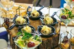 Härlig dekorerad sköta om banketttabell med olika matmellanmål och aptitretare Canape rullar i små pannor på trä Royaltyfria Bilder