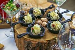 Härlig dekorerad sköta om banketttabell med olika matmellanmål och aptitretare Canape rullar i små pannor på trä Royaltyfri Fotografi