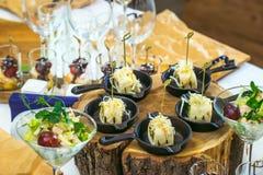 Härlig dekorerad sköta om banketttabell med olika matmellanmål och aptitretare Canape rullar i små pannor på trä Fotografering för Bildbyråer