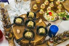 Härlig dekorerad sköta om banketttabell med olika matmellanmål och aptitretare Canape rullar i små pannor på trä Arkivfoto